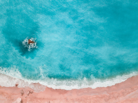 Soft blue waves of the sea with white foam on sandy beach toned trendy living coral color of year 2019 shoot from drone.