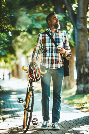 A handsome young man goes to the city ride with his bike, walking with coffee beside it and thinking about where he would go.