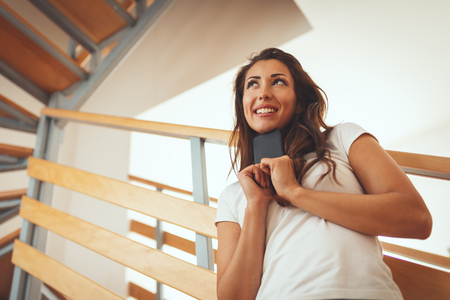 A happy smiling young woman stands in the living room of her new apartment in front of the stairs holding smartphone. Stok Fotoğraf