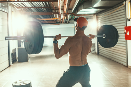 Young muscular man is doing snatch or shoulder press exercise with barbell on hard training at the garage gym.