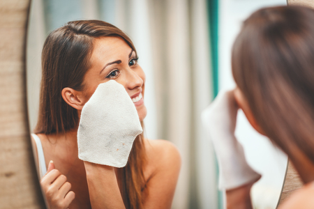 Beautiful young smiling woman is removing make up with facial wipe in front of her bathroom mirror.