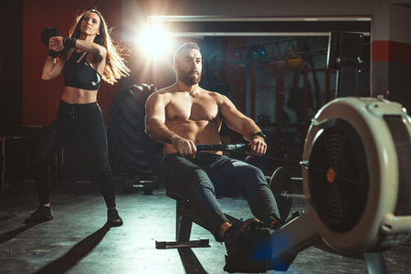 Beautiful young muscular couple is having workout at the gym. Handsome man is pulling the rowing machine, and attractive girl exercising with dumbbell.