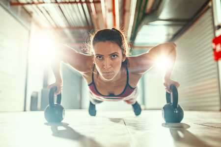 Young muscular woman is doing push-up exercise on a kettlebells as hard training in the garage gym. Imagens