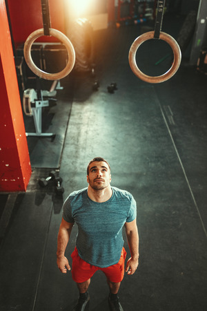 Young muscular man is preparing to do exercise on gymnast rings at the gym. Stock Photo - 124710225