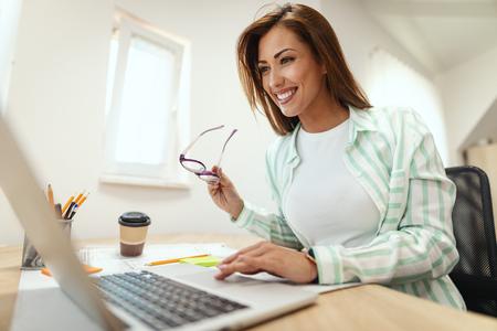 Jonge lachende zakenvrouw werkt op de computer op kantoor. Ze is op zoek naar iets op de laptop.