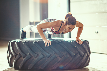 Young muscular woman is doing push-up exercise on a tire at cross fit training in the garage.