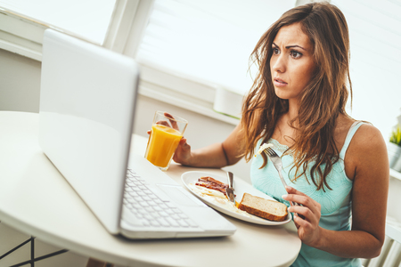 Beautiful young dreamy woman is enjoying and relaxing in the morning, eating healthy breakfast, looking at laptop and cant quite wake up.