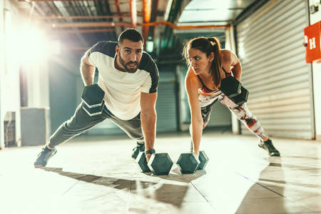 Young muscular couple is doing strength exercise on cross fit workout at the garage.