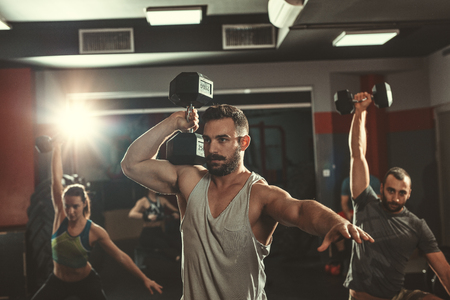 Several young friends are doing hard exercise with dumbbells at the gym. Focus is on young man, on foreground. Stock Photo - 124710252