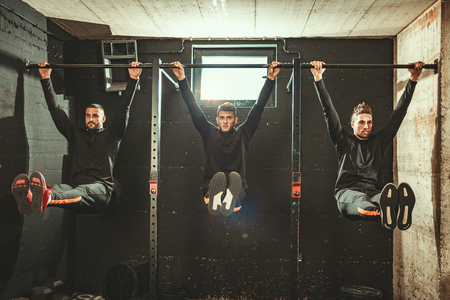 Three strong young muscular men are doing pull-up exercises at the gym.