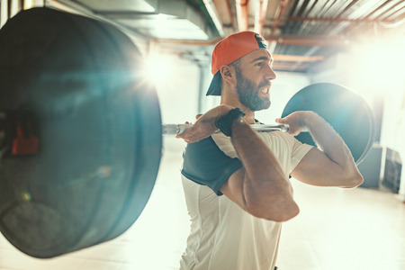 Young muscular man is doing high pull exercise with barbell on cross training at the garage gym.