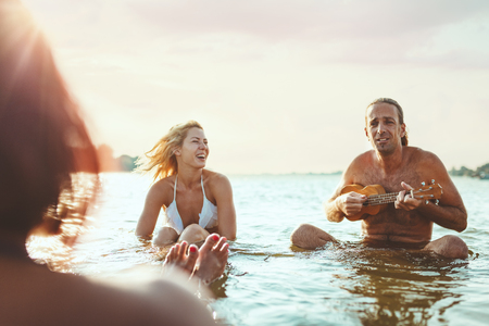 Happy young people having a great time together at the beach. They are sitting in the water and man is playing ukulele and singing. Sunset over water. 版權商用圖片 - 124710183