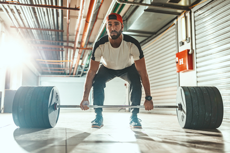 Young muscular man is ready to deadlift exercise at the garage gym.