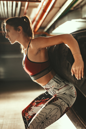 Young muscular woman is doing hard exercise with tire on cross fit training at the garage. Imagens
