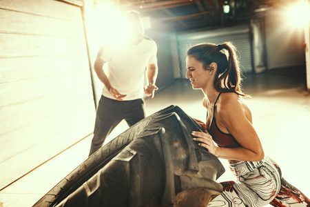 Young muscular woman is flipping a tire on hard training with personal trainer at the garage gym.
