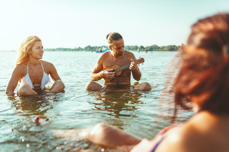 Happy young people having a great time together at the beach. They are sitting in the water and man is playing ukulele and singing. Sunset over water. 版權商用圖片 - 124710151