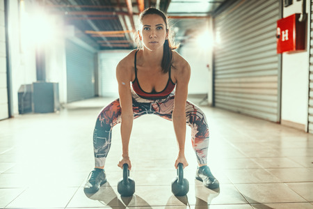 Young muscular woman is exercise with kettlebells on hard training at the garage gym. Stock Photo