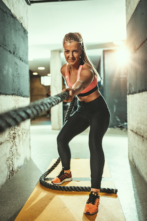 Young muscular woman is exercising with ropes at the  gym. Selective focus. Imagens