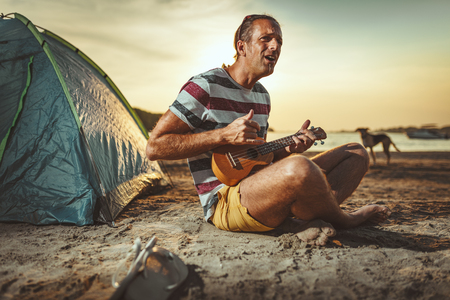 Happy young musician has a great time at the beach. He is sitting by the river, playing ukulele and singing at sunset. 版權商用圖片 - 124710163