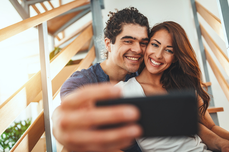 The young couple is moving into a new house. They are resting after bringing boxes with things to their new home and taking selfie sitting at stairs.