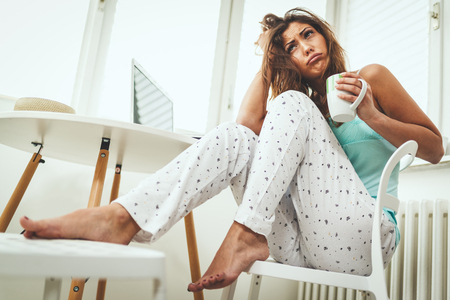 Beautiful young dreamy woman is drinking coffee in the morning and can't quite wake up. Reklamní fotografie - 124710118