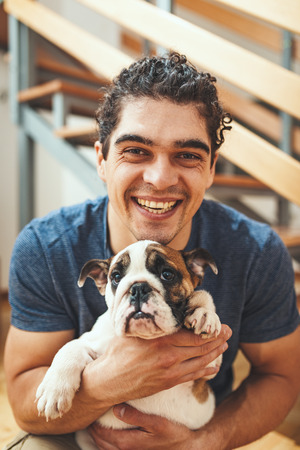 A happy smiling young man is sitting on a floor in the living room of his new apartment and holding a little puppy.