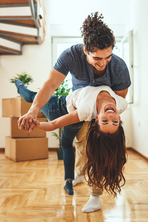 The young happy couple is moving into a new house. They are unpacking boxes with things in their new living room and having fun. Stok Fotoğraf