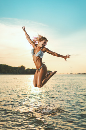 A young happy woman has a great time at the beach. She is having fun and jumping over the water. 版權商用圖片 - 124710087