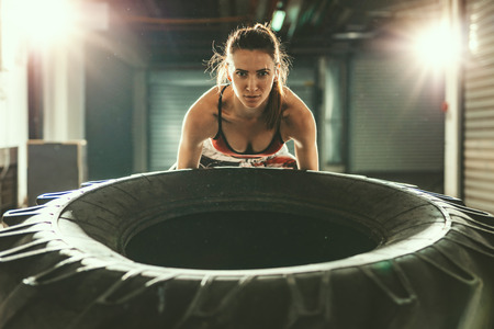 Young muscular woman is flipping a tire on cross fit training at the garage.