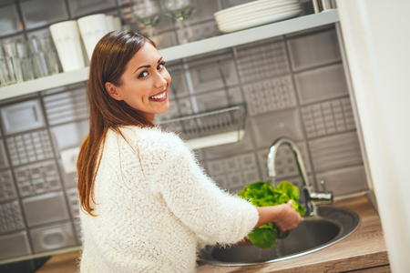 Beautiful young smiling woman is washing lettuce in her kitchen.