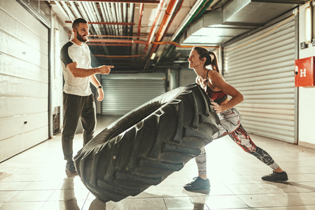 Young muscular woman is flipping a tire on hard training with personal trainer at the garage gym. Stock Photo - 124710063