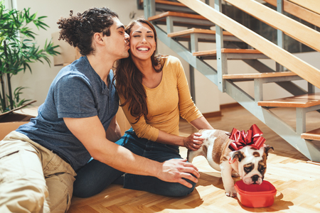 The young happy couple is moving into a new house. They are feeding their little puppy after they brought boxes with things to their new home. Stok Fotoğraf