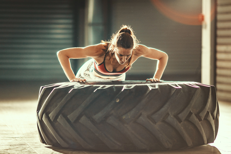 Young muscular woman is doing push-up exercise on a tire at cross fit training in the garage. Stock Photo - 124710068
