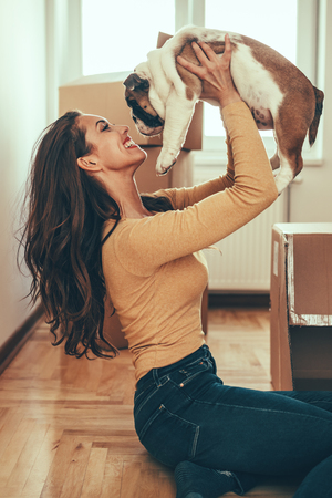 A happy smiling young woman is sitting on a floor in the living room of her new apartment and holding a little puppy. Stok Fotoğraf