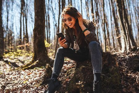 Cute smiling young woman, with smartphone in her hand and headphones on her head, is sitting on the fall leaves in early autumn sunny day and listening music. 版權商用圖片
