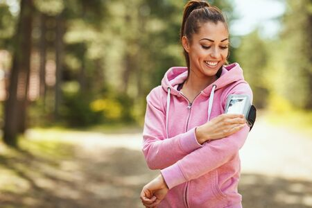 Happy woman, wearing sportswear, checking her smartphone in a break of exercises in a sunny forest, enjoying landscape among the trees.