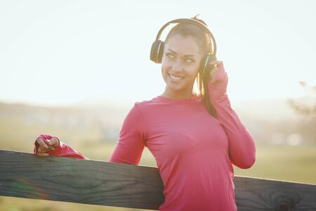 Young cute female runner listening to music and preparing to jogging at morning in mountains. Stock Photo