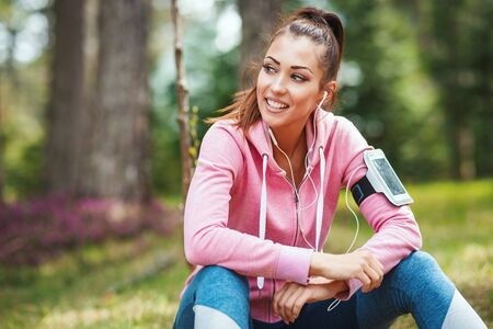 Happy woman, wearing sportswear, listening music in a break of exercises in a sunny forest, enjoying landscape among the trees.