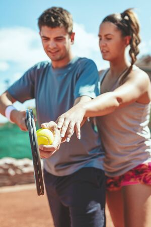 Beautiful young woman with her trainer practicing serve on outdoor tennis court. Foto de archivo