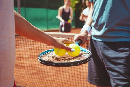 Close-up of a couple tennis player before serving to tennis match on outdoor clay court. Selective focus. Focus on a hands who holding ball and racket.