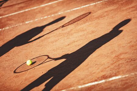 Shadow of a tennis ball and tennis player in action on a clay court . Banque d'images
