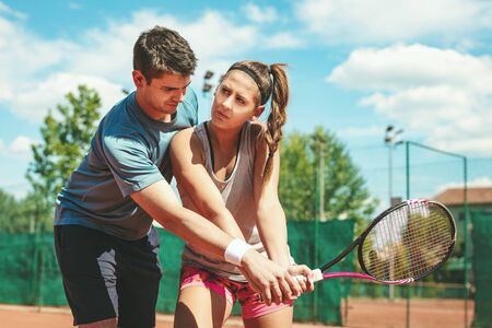 Beautiful young woman with her trainer practicing tennis on outdoor court.