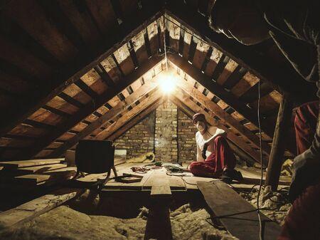 Zwei Mann reparieren alte Dachkammer am Haus. Standard-Bild