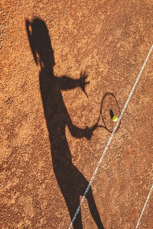 Shadow of a tennis ball and tennis player in action on a clay court . Imagens