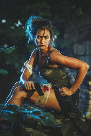 Beautiful young woman holding gun and getting ready for the attack in abandoned ruin. Banque d'images