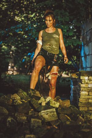 Beautiful female special forces holding gun and getting ready for the attack in abandoned ruin.