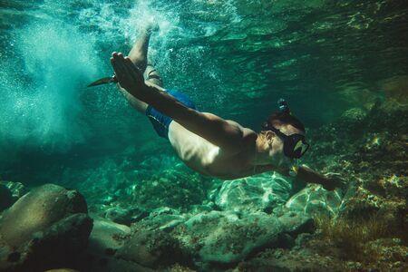 Gutaussehender Mann, der sich im Sommerurlaub amüsiert und den Meeresboden beim Tauchen im Meer erkundet. Standard-Bild