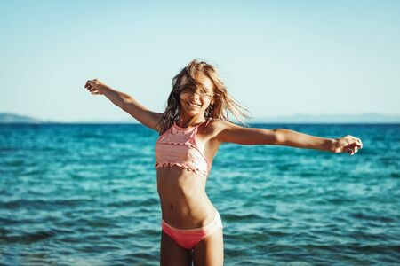 Cute teenager girl having fun on the beach and grabs the last rays of the sunset sun. Imagens - 129204976