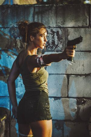 Serious attractive female special forces holding gun and getting ready for the attack in abandoned ruin.