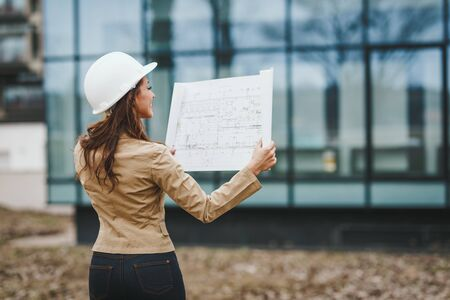Successful young female engineer with white helmet checked new project and analyzing blueprints in front of construction site. Stock fotó